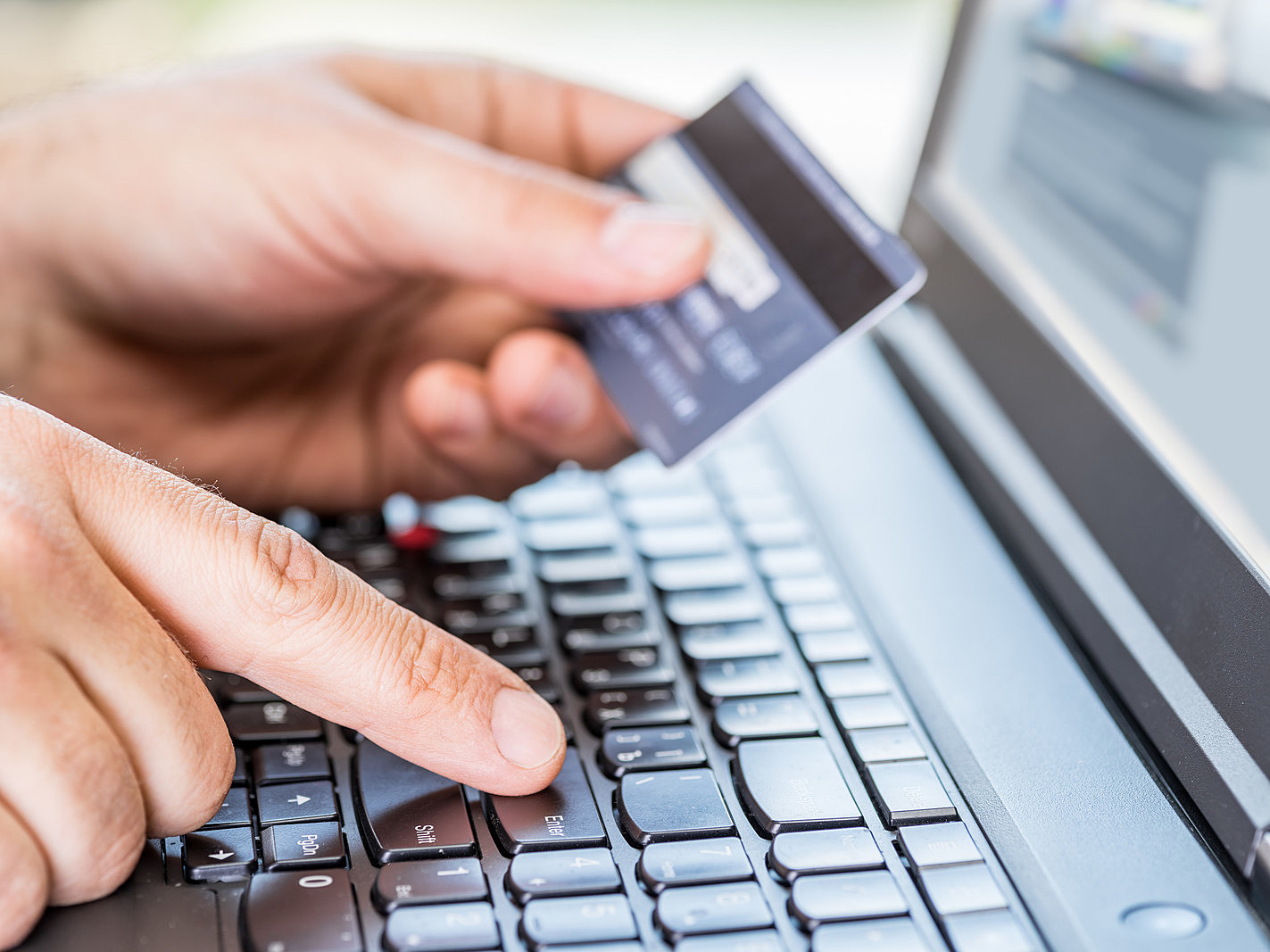 Online shopping using credit card and laptop.